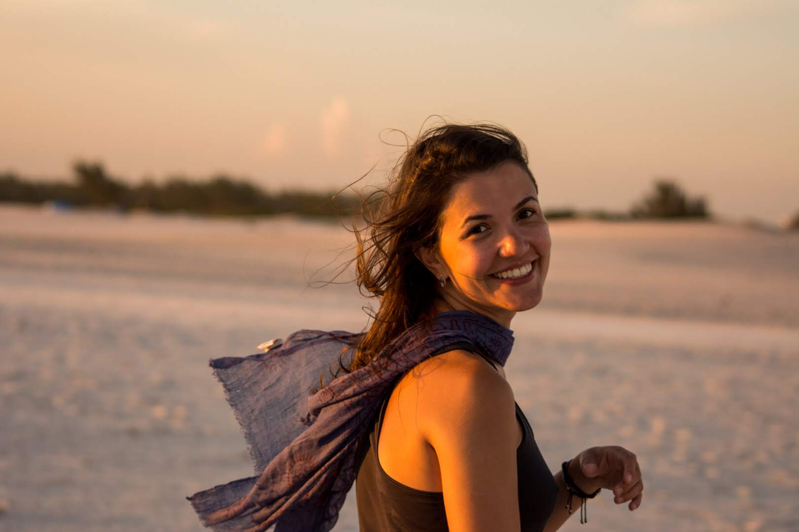 wonderful sunset portrait photo shooting. Beautiful girl at the beach smiling with the wind in her hair