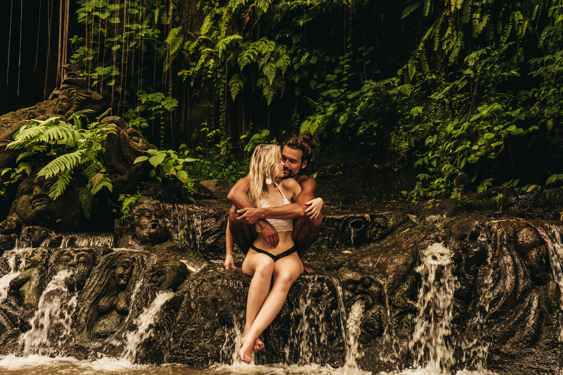 couple photo shoot. boy and girl sitting in flowing water hugging each other in the middle of nature