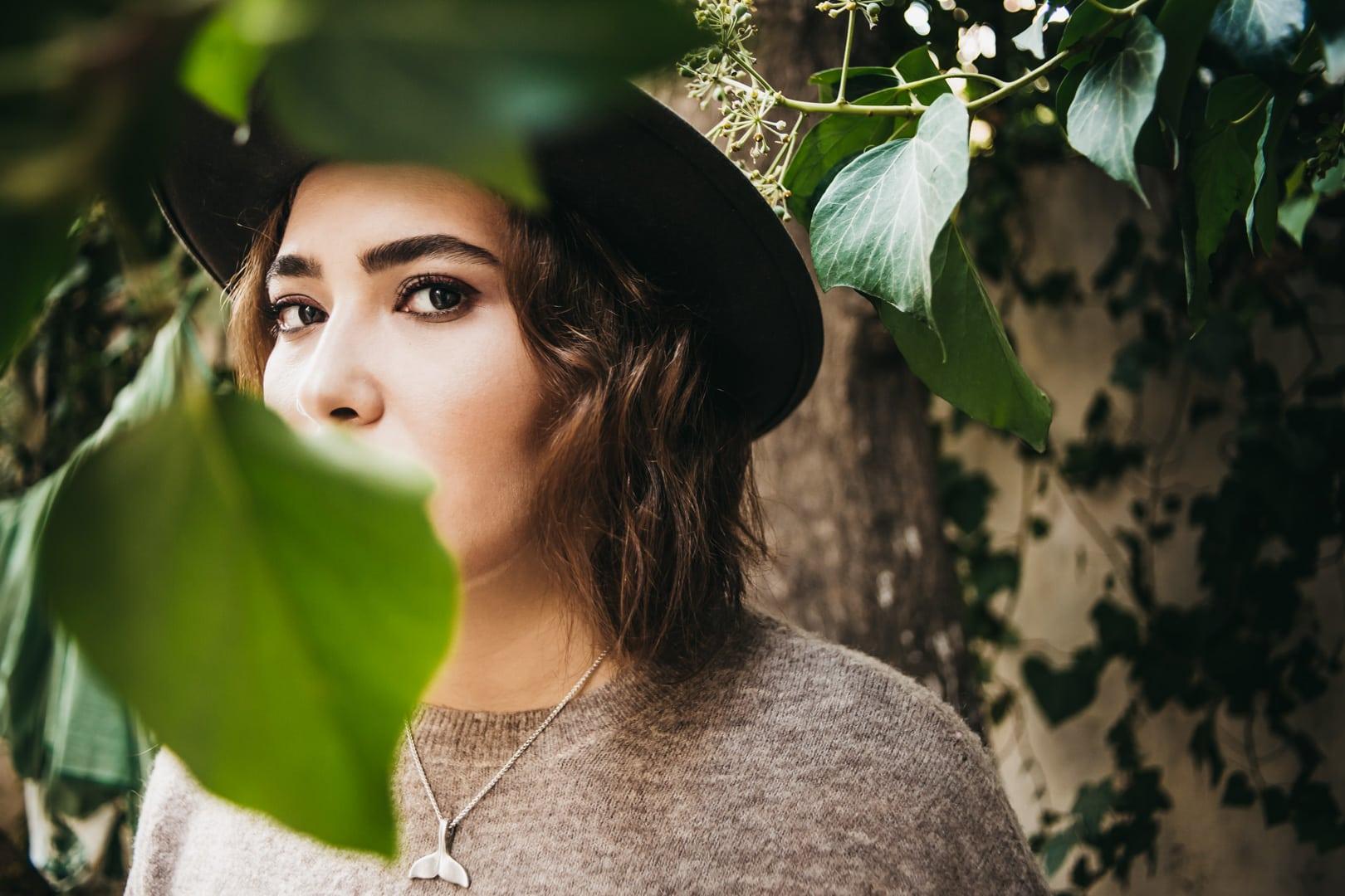 algarve portugal portrait photo. girl with hat hiding behind a leaf