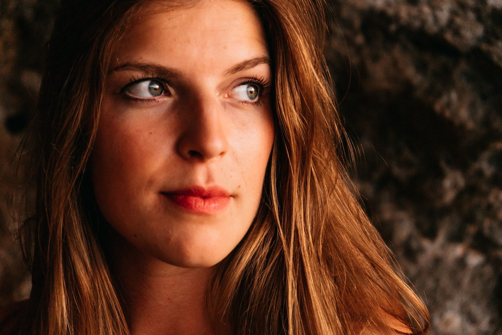 Beautiful portrait photo session in Algarve. Close up of a blonde girl in a cave looking to the right.