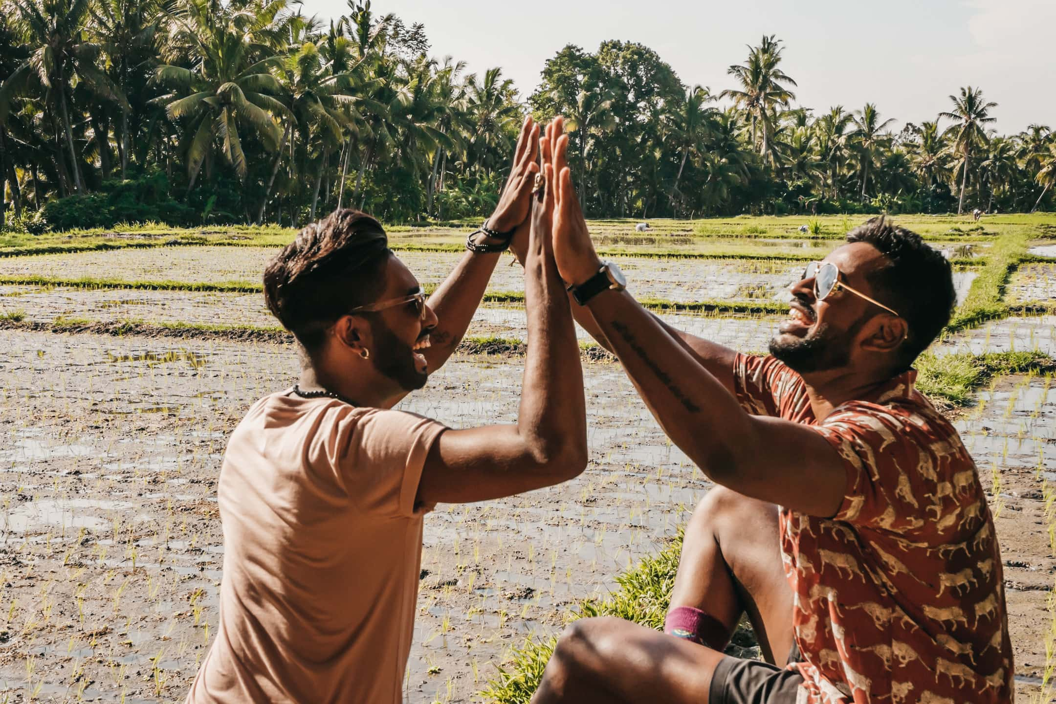 Couple photo shoot. two men having fun and giving high five in the rice fields